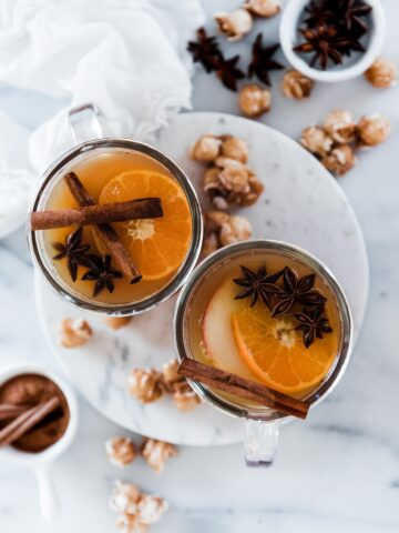 Mulled cider in glass mugs. There is caramel corn surrounding.